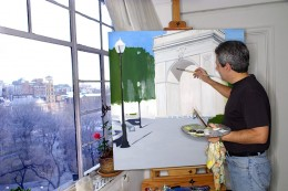 Artist painting by windows